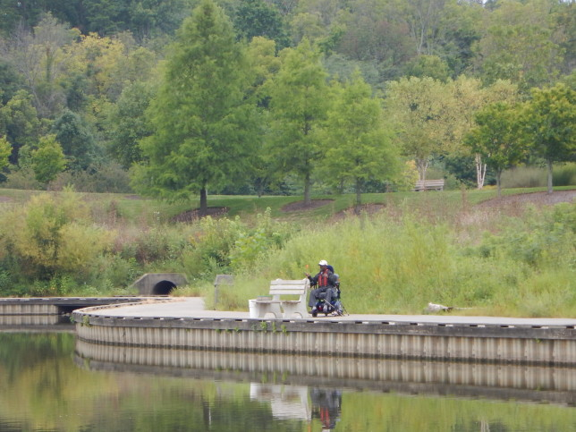 Man fishing along lakeshore seated in wheelchair.