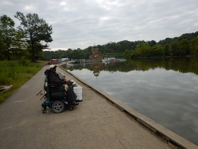 Man fishing along lakeshore seated in wheelchair next to park bench with fishing gear.