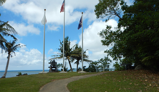 Paved asphalt trail overlooking pacific, a Japanese defense gun and the American flag and Guam flag.