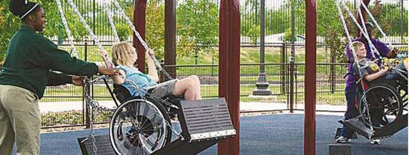 Child in wheelchair being pushed on metal platform swing. Words stricken share if you think this belongs in all parks. Replaced with Nope. Not a good idea. Read more about why.